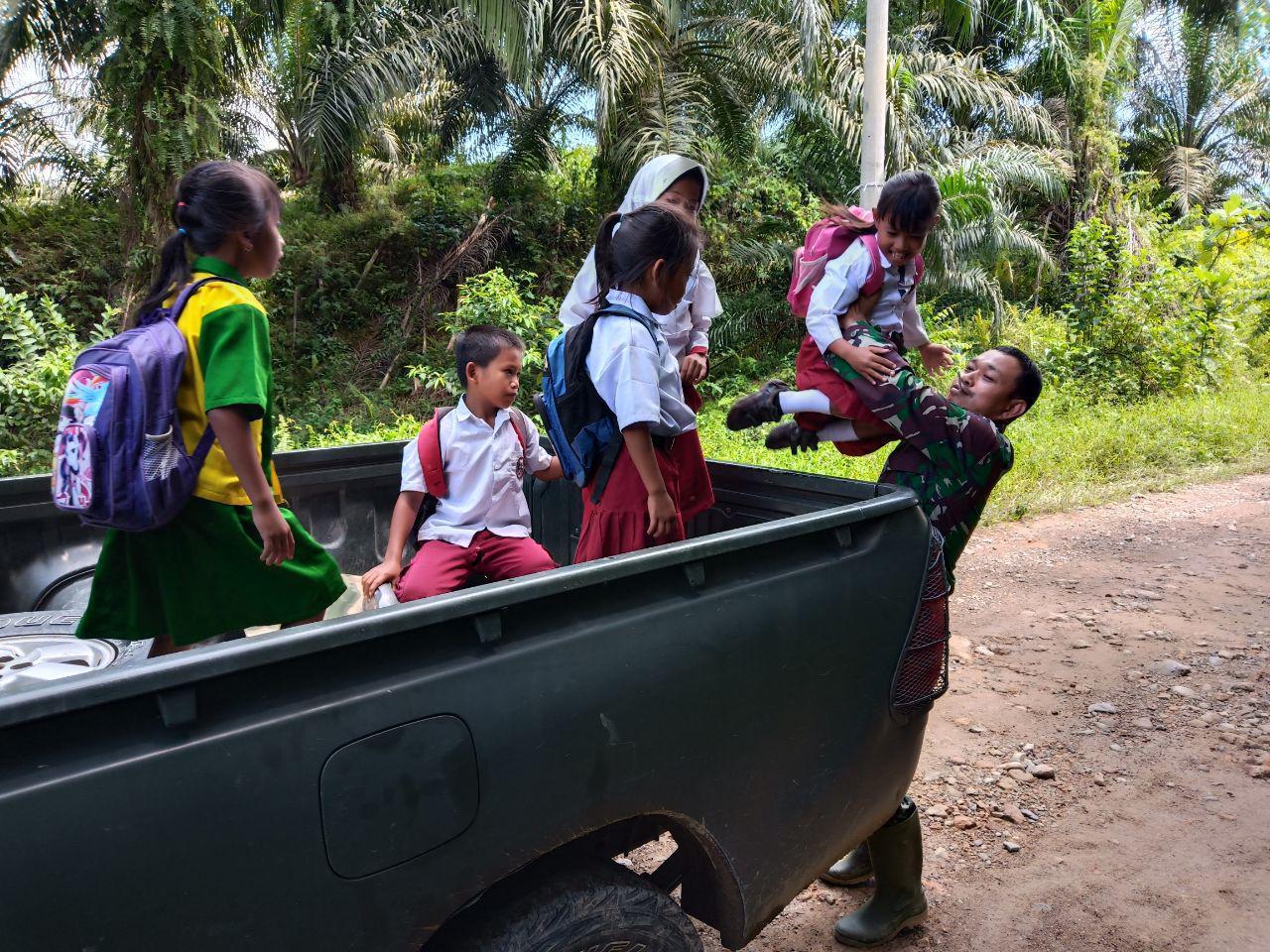 Di Lokasi TMMD Personil Kodim 1418/Mamuju Mengantar Pelajar ke Sekolahnya