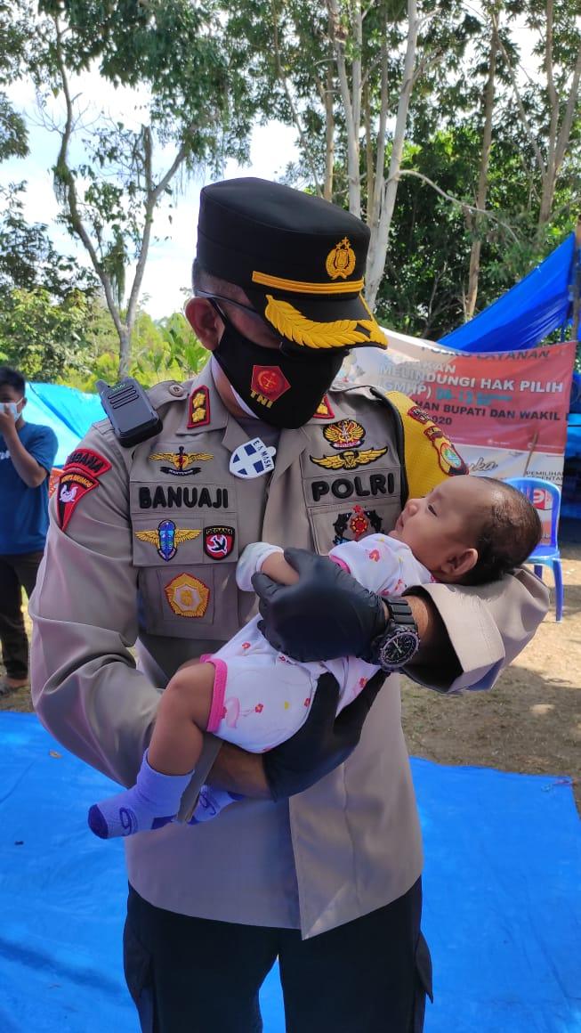 Gendong Bayi di Pengungsian Desa Lombang, Kapolres Majene Titipkan Harapan dan Doa